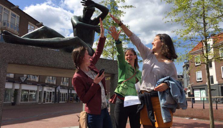 Team geeft elkaar een high five tijdens een dagje uit Arnhem