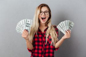 Vrouw met heel veel geldbiljetten in de handen