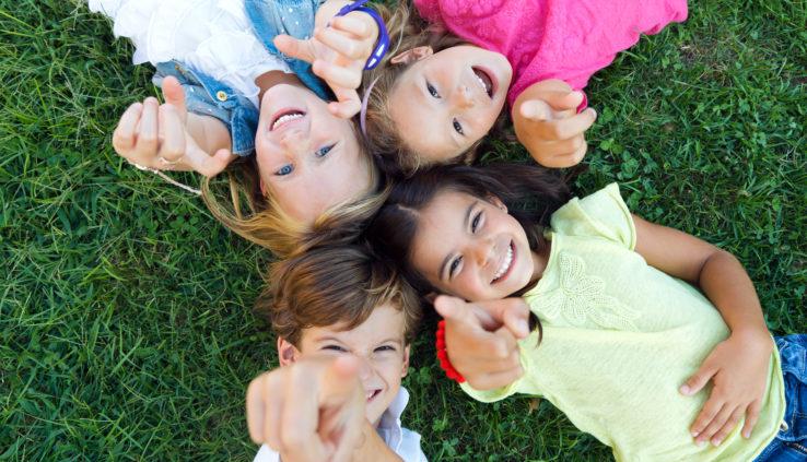 Wil jij deze vakantie de hand op de knip houden, maar niet elke dag binnen zitten met de kids? Bekijk dan hier onze beste Goedkope uitjes met kinderen. Hier liggen de kinderen in het gras en wijzen lachend naar boven.